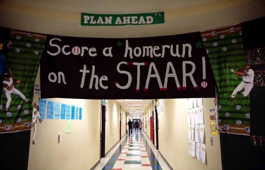 """A handmade banner reading, """"Score a homerun on the STAAR"""" hangs above a school hall entryway."""