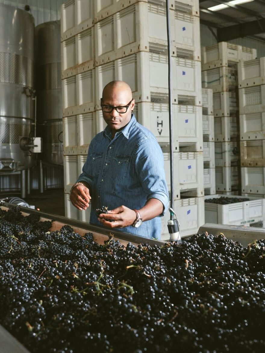 Andre Mack looks at grapes.