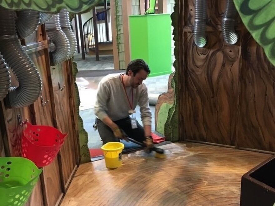 A worker at the Children's Museum of Richmond cleans an exhibit in preparation for the re-opening.