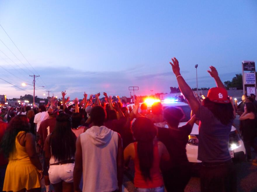 Protesters on West Florissant surround a police car on August 9, 2014. Looting broke out shortly afterward.