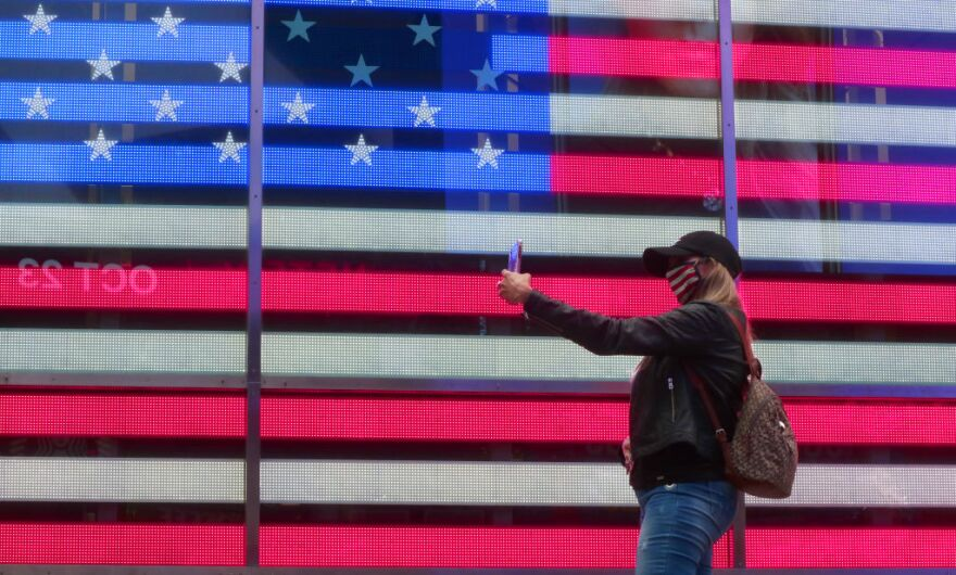 A person in a mask takes a selfie in front of the American flag on October 22, 2020, in New York City. (Gary Hershorn/Getty Images)