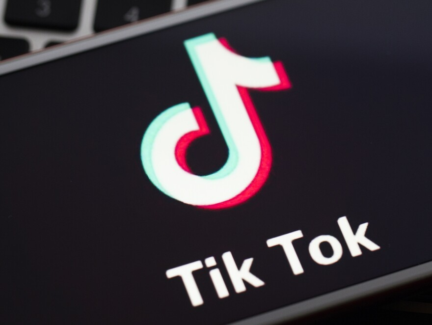 In this photo illustration a mobile phone screen displays TikTok logo in front of a keyboard.