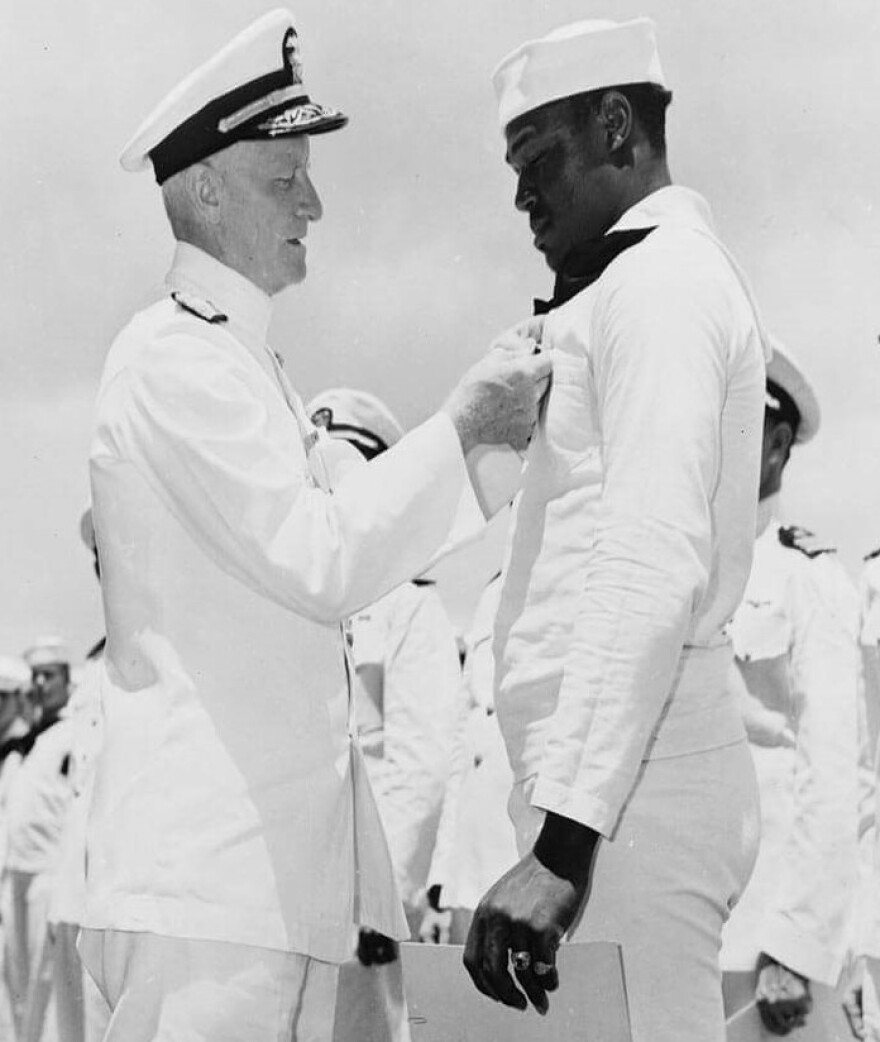 "Doris ""Dorie"" Miller, receiving the Navy Cross from Admiral Chester Nimitz, the Commander in Chief, Pacific Fleet, during a ceremony on board the USS Enterprise on May 27, 1942."