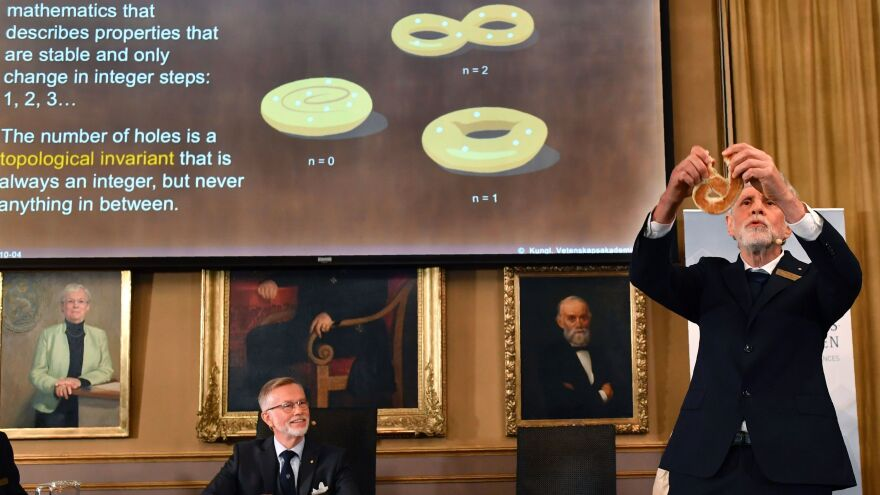 Thors Hans Hansson, member of the Nobel Committee for Physics, uses a pretzel to visualize his explanations of topology during a press conference at the Royal Swedish Academy of Sciences in Stockholm on Tuesday, as the permanent secretary of the Royal Swedish Academy of Sciences, Goran K Hansson, watches.