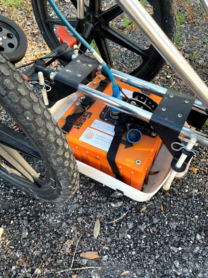 The ground penetrating radar is orange and the size of a large car battery, riding in a cradle that resembles a baby stroller