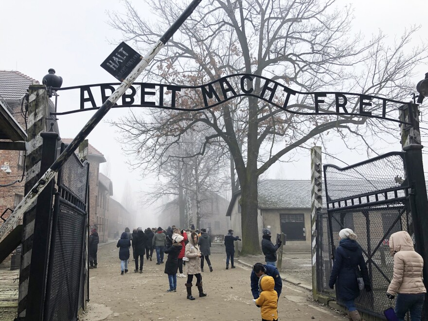 "The front gate of the former Auschwitz death camp, now a museum, reads <em>Arbeit macht frei, </em>""Work sets you free."" More than 2 million people visit the Auschwitz museum each year."