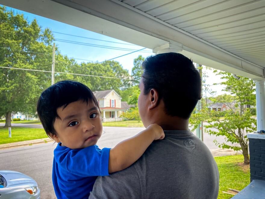 Marcial holds baby Sergio at home