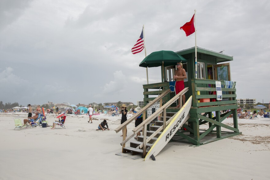A green lifeguard stand on Siesta Beach, with a few people milling about.