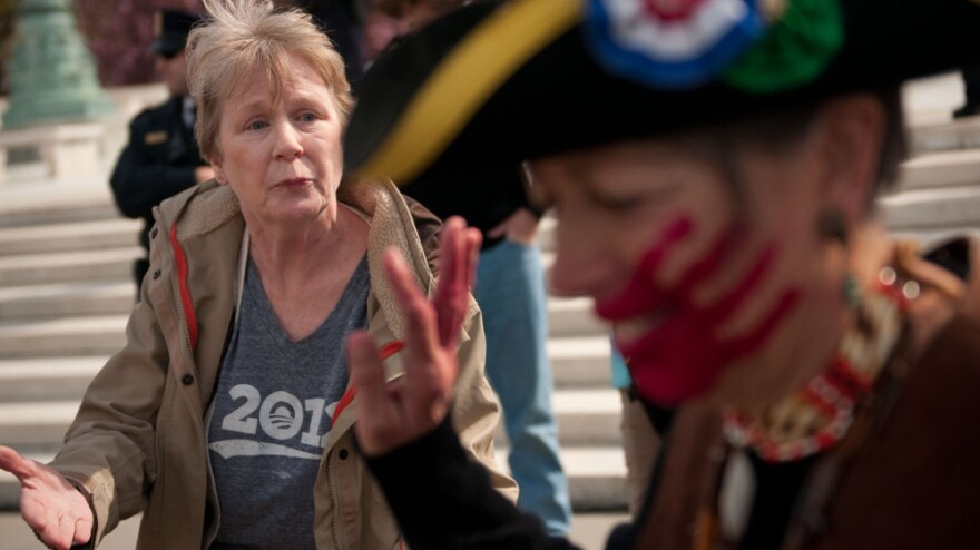 Holly Harness (left), a supporter of the health care law, argues with Susan Clark, an opponent of the law, outside the Supreme Court on Wednesday.