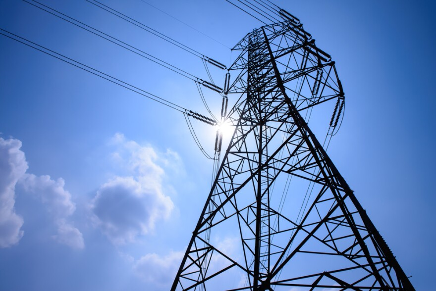 A powerline transmission tower. Blue skies are in the background.