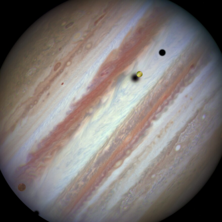 An image captured by the Hubble Space Telescope as three of Jupiter's largest moons parade in front of the gas giant on Feb. 5, 2015. On the left is the moon Callisto and on the right, Io. The shadows from Europa, which cannot be seen in the image, Callisto and Io are strung out from left to right.