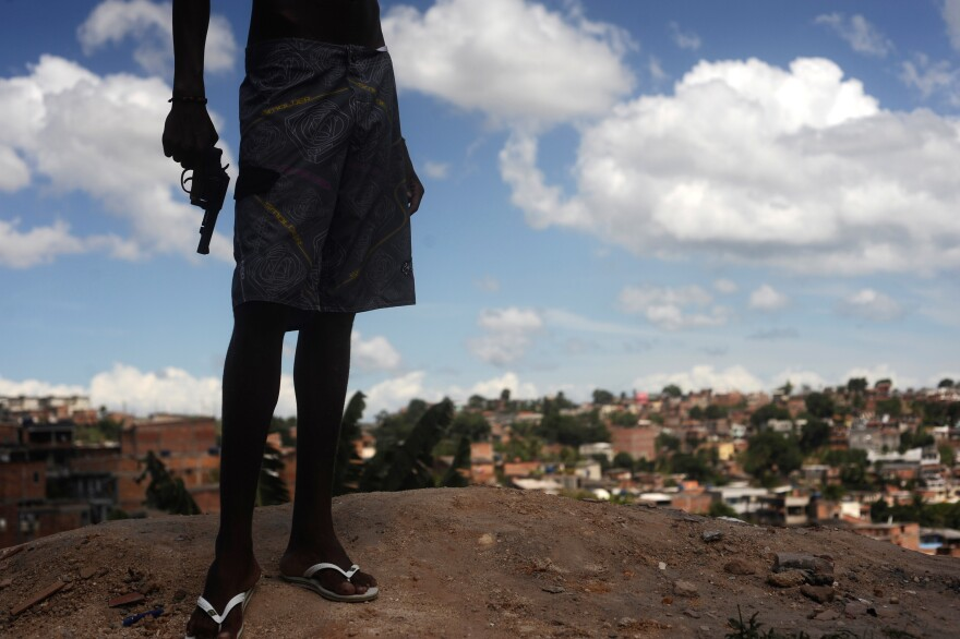 A Brazilian drug gang member nicknamed Giant, 17, poses with a gun atop a hill overlooking a poor neighborhood in Salvador, Brazil, in 2013.