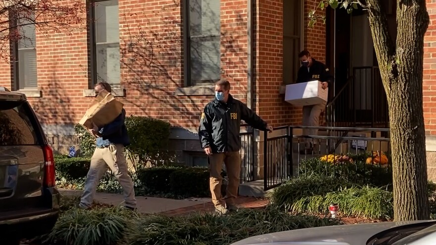 FBI agents carry boxes out of the Columbus home of Public Utilities Commission Chair Sam Randazzo.