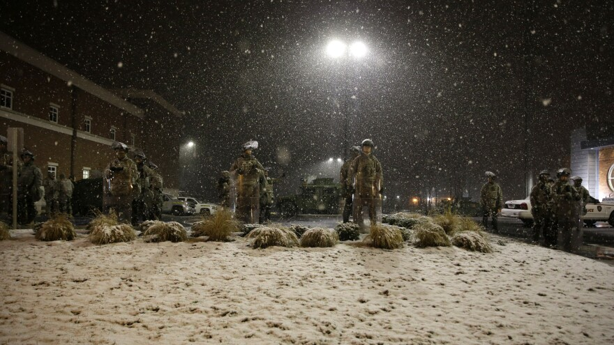 Snow falls Wednesday night as Missouri National Guard members stand outside of the Ferguson Police Department in Ferguson, Mo.