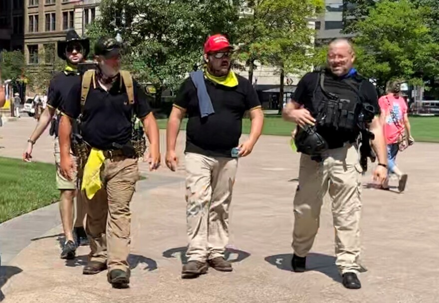 """Some demonstrators at an anti-mask rally at the Statehouse in July. Event planners said security would be provided by """"militia"""". Proud Boys are often identified by black collared polo shirts with yellow stripes on the sleeves."""