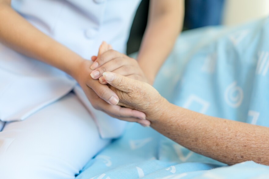 A young woman sits at the bedside of an elderly woman. The young woman holds the elderly woman's hand.