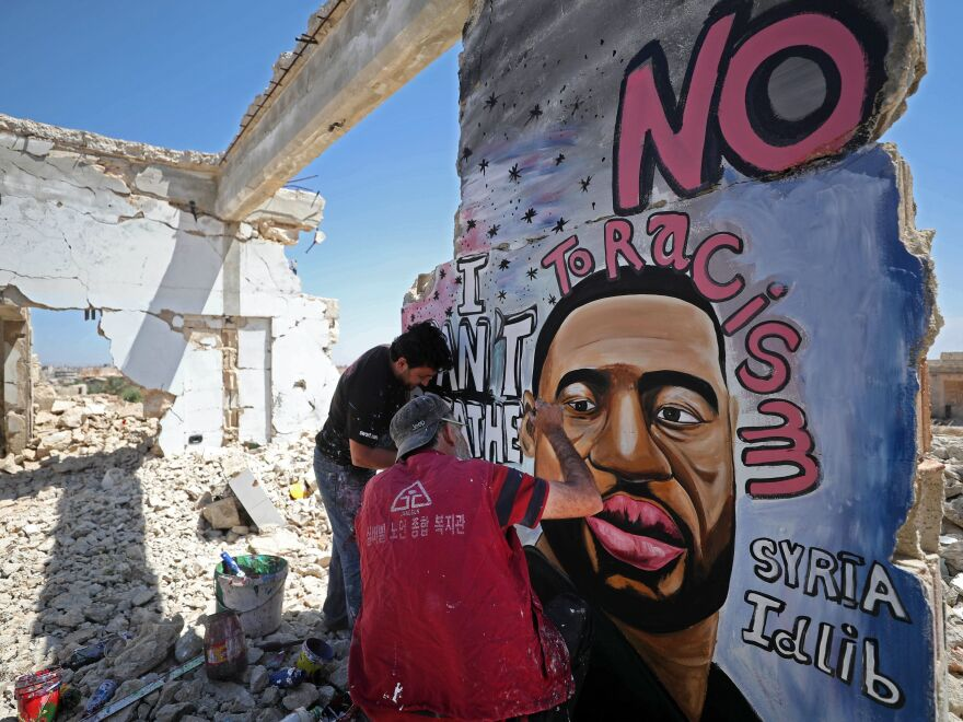 Syrian artists Aziz Asmar and Anis Hamdoun paint a mural depicting George Floyd in the town of Binnish in Syria's northwestern Idlib province on June 1, 2020.