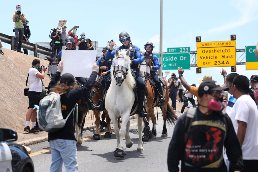 A police officer leading a mounted unit prepares to pepper spray protesters on an Interstate 35 access road in downtown Austin.