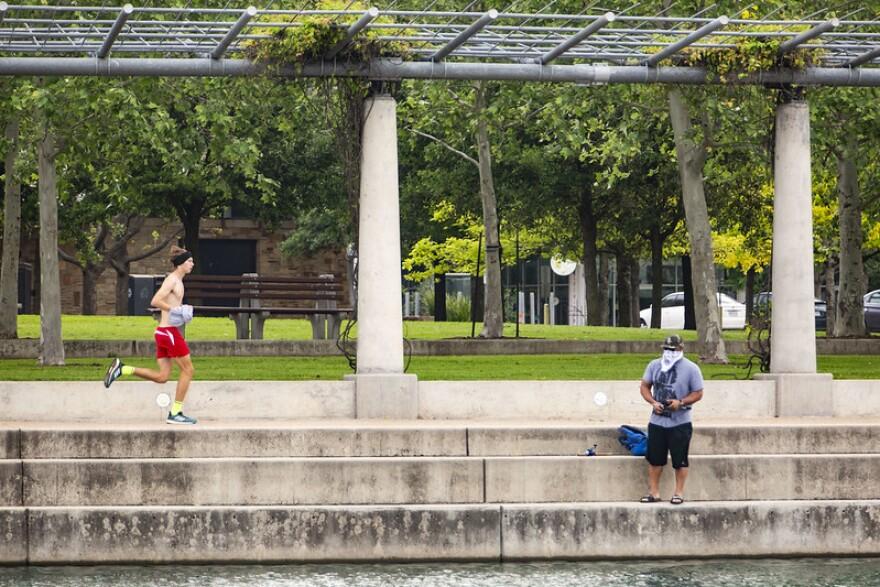 A man fishes and a man runs near Mueller Lake Park during the coronavirus pandemic.