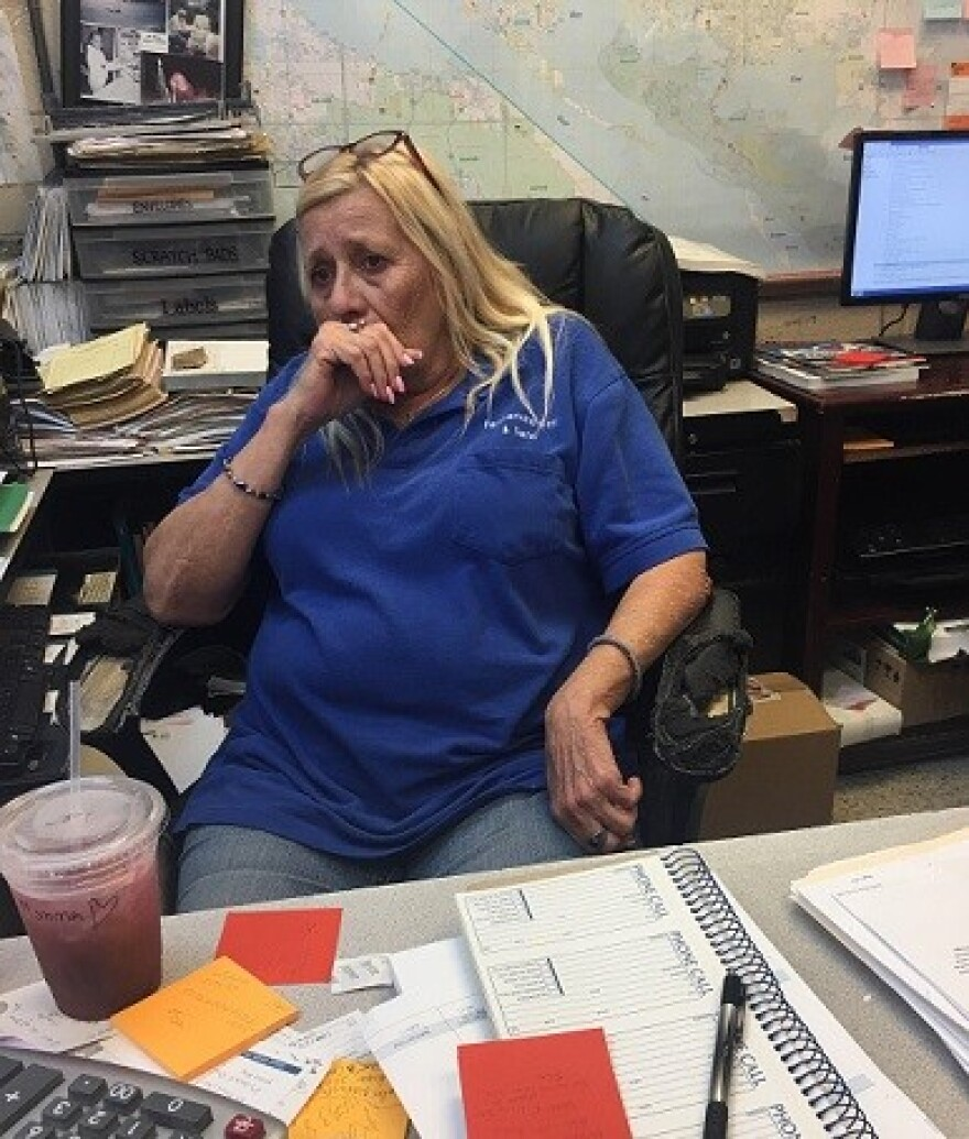 Panama City resident Judy Woodruff sits at her desk at work and tears up as she talks about Hurricane Michael damage and the difficult recovery.