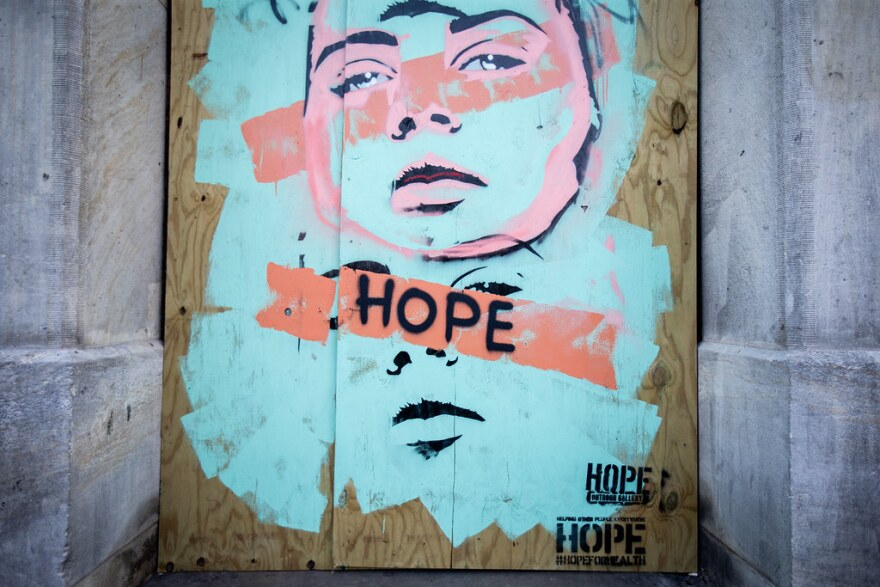 "A mural that says ""Hope"" painted on a boarded-up business on Sixth Street."