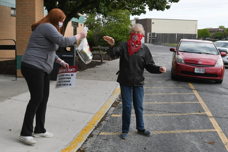 Picture of a woman wearing a bandana over her mouth waves goodbye to a library worker holding a bag of returned materials