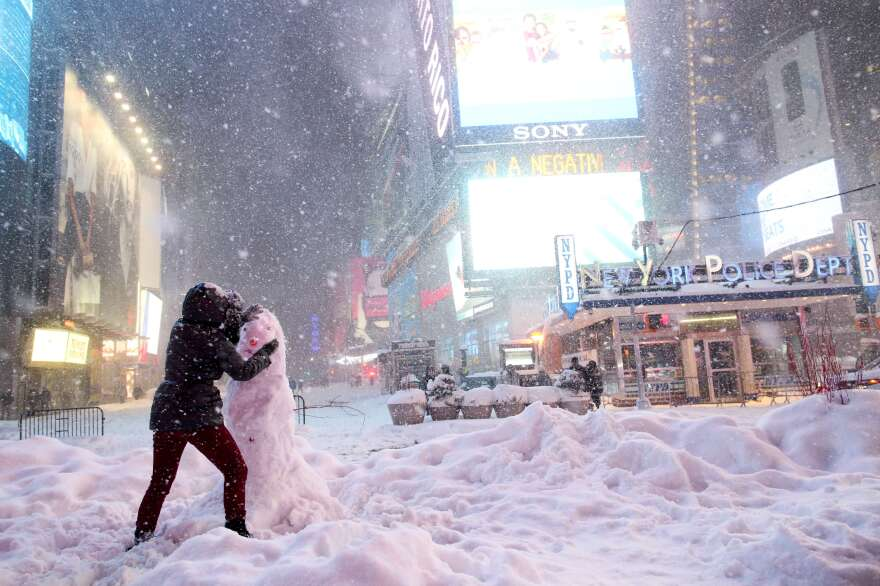 A woman decorates a snowman in Times Square on Saturday, while all cars but emergency vehicles were banned from driving on the road. The travel ban was lifted Sunday morning.