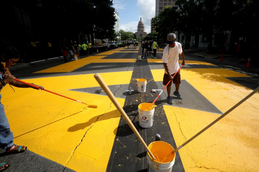 """Painters outline """"Black Austin Matters"""" on Congress Avenue early Tuesday morning."""