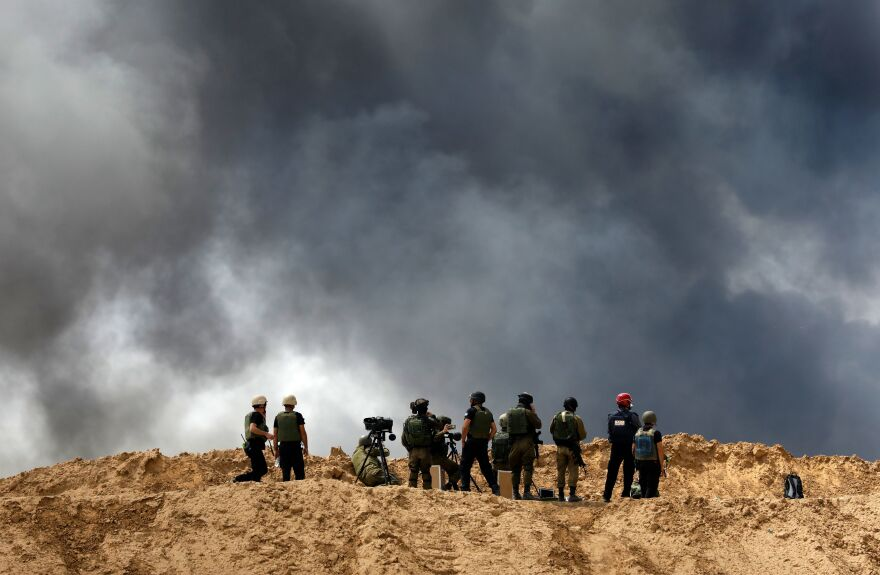 Israeli security forces deployed near the Israeli border with the southern Gaza Strip watch smoke rising from the Palestinian village of Khuzaa.