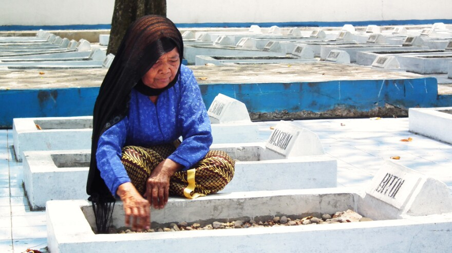 <p>Cawi Binti Baisan, 84, squats beside the grave of her first husband, Bitol, a farmer who was executed by Dutch soldiers in 1947. She is one of seven remaining widows of the more than 400 estimated massacre victims. A Dutch court recently ruled that the Dutch government must compensate the widows for their losses.</p>