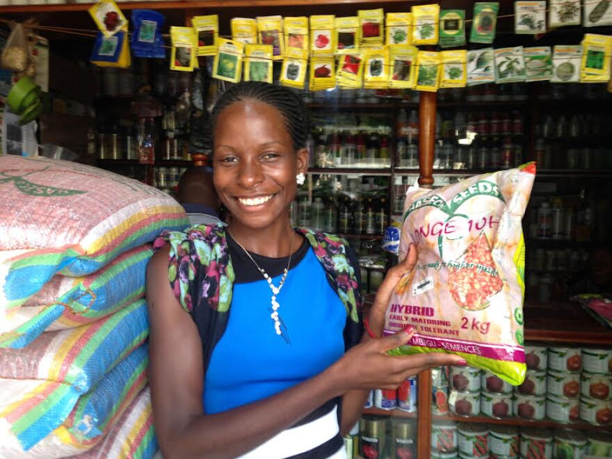 Annet Nakkide holds up a package of Longe 10-H, developed for the Drought Tolerant Maize for Africa Initiative.