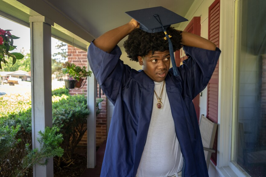 Jhalen Taylor, 18, tries to get his graduation cap to fit outside his mom's Florissant home May 31, 2020, before attending an outdoor graduation.