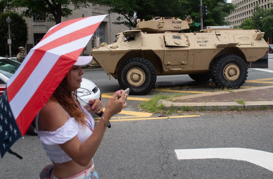 A woman takes a photo near an armored military vehicle during the Fourth of July parade in Washington, D.C.