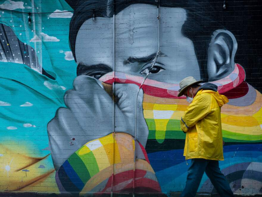 Health experts say they're not yet sure about the level of immunity people may have after recovering from COVID-19. Here, a man wears a protective mask as he passes a mural in New York City, where the COVID-19 death toll has passed 10,000.