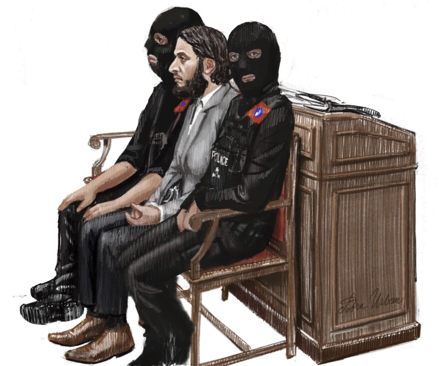 In this courtroom sketch, Salah Abdeslam (center) sits between two police officers at the Brussels Justice Palace in February. He was sentenced Monday to 20 years in prison over charges related to a shootout when he resisted arrest months after the 2015 Paris attacks.