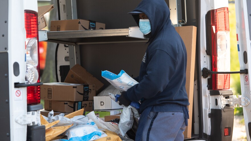 A mailman wearing a mask and gloves to protect himself and others from the coronavirus loads a postal truck with packages in Washington, D.C., Thursday.