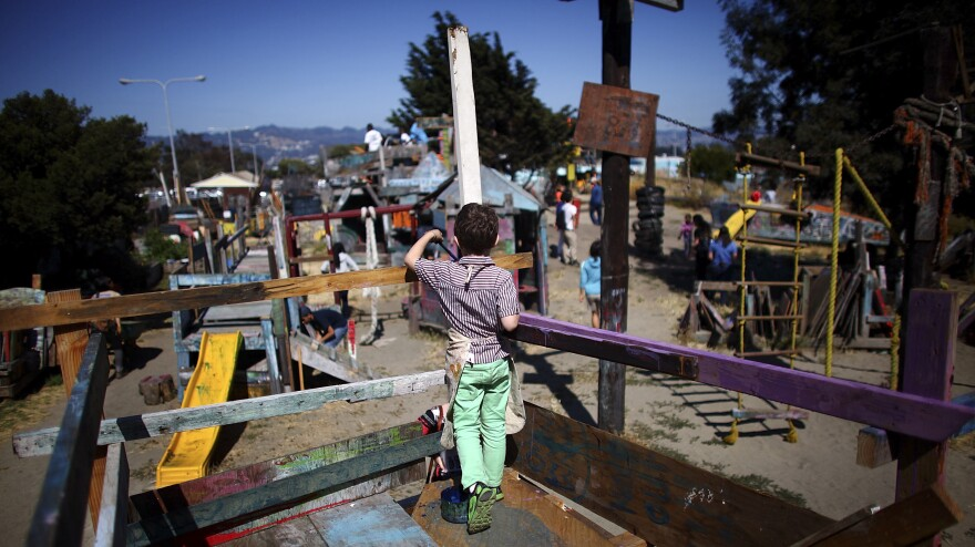 A boy paints the railings of a wooden fort at the Berkeley Adventure Playground. Nails, hammers, and buckets of paint are just part of the fun.