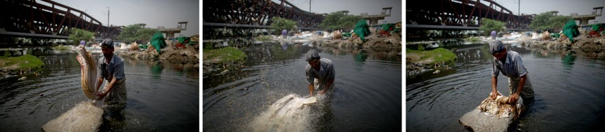 """Mohammad Zamir, 38, washes pieces of cloth on the banks of the Yamuna River. He stands in the toxic water from 6:30 in the morning until 7 at night. Deflecting any talk of health issues, Zamir says his elders did the same work and lived a """"long life."""""""
