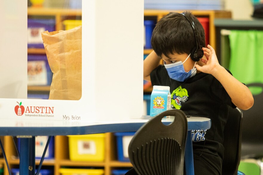 a young student wearing a face mask and head phones