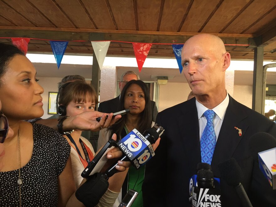 Florida Gov. Rick Scott takes reporters' questions after a roundtable discussion with elected officials, public health officials and business leaders in Miami's Wynwood neighborhood.