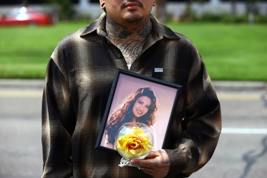 Gus Salazar holds a photo of Selena Quintanilla-Perez in Corpus Christi, Texas, as fans gathered in March to remember the Latin pop star on the 20th anniversary of her death.