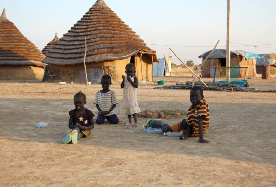 <p>Children in South Sudan, one of the world's poorest nations, sit in front of traditional homes made of mud and thatch.</p>