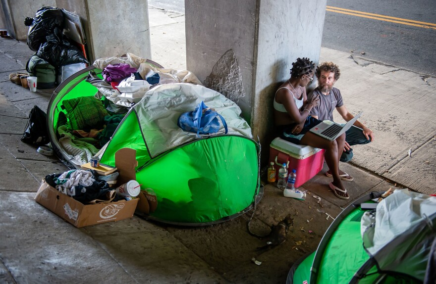 """Social worker Matthew Reed (right) talks with Lawson near her tent home in downtown Atlanta. Reed says,""""This is what street medicine is about: going out into these areas where people are not going to seek attention until it's an emergency."""""""