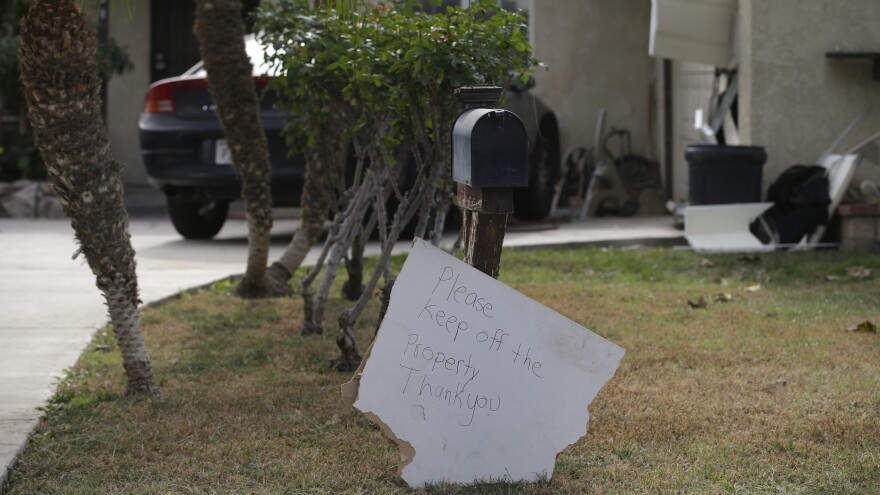 A sign stands in front of a mailbox at Enrique Marquez's home last week in Riverside, Calif. Authorities say Enrique Marquez, an old friend of San Bernardino attacker Syed Farook, purchased two assault rifles used in this month's fatal shooting.