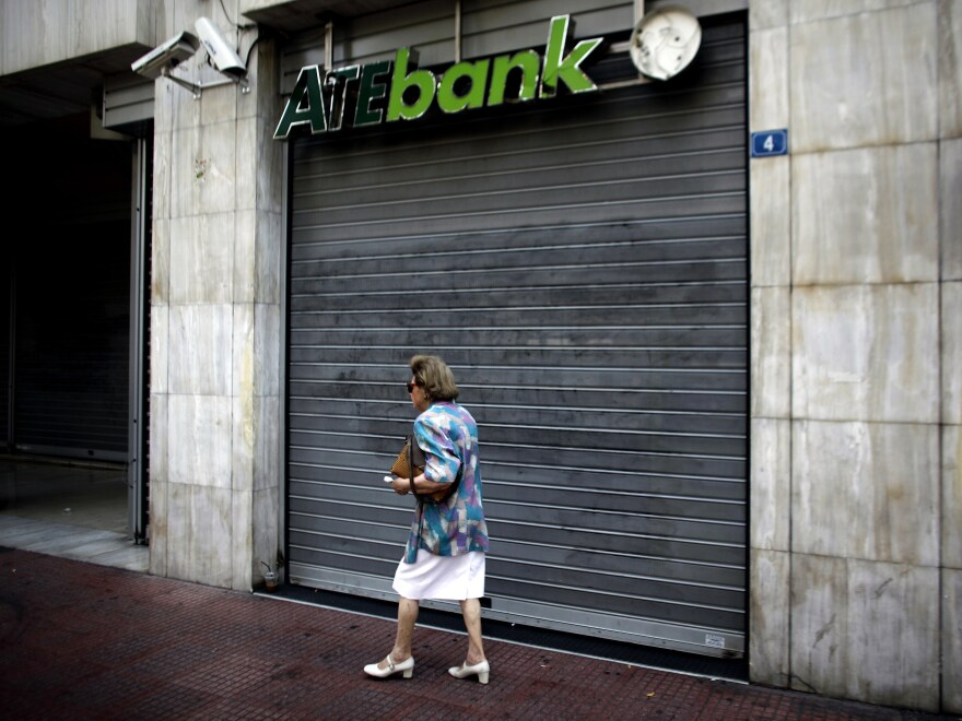 A woman walks past a closed branch of the ATE bank in Athens, on July 30 as employees of the bank went on strike.