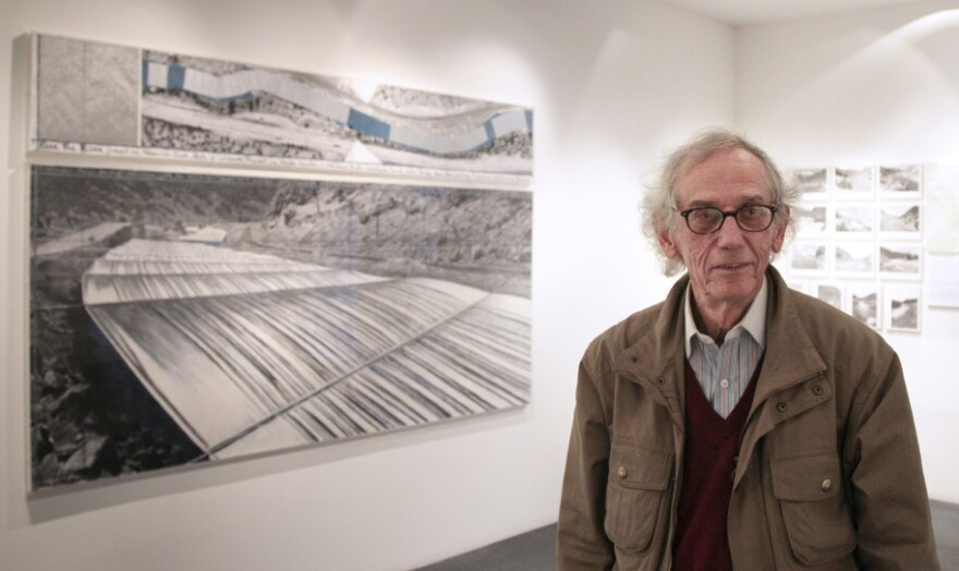 Christo stands next to one of his works at a 2010 exhibition in Paris about the <em>Over the River</em> project. If approved, the installation could begin in the fall.
