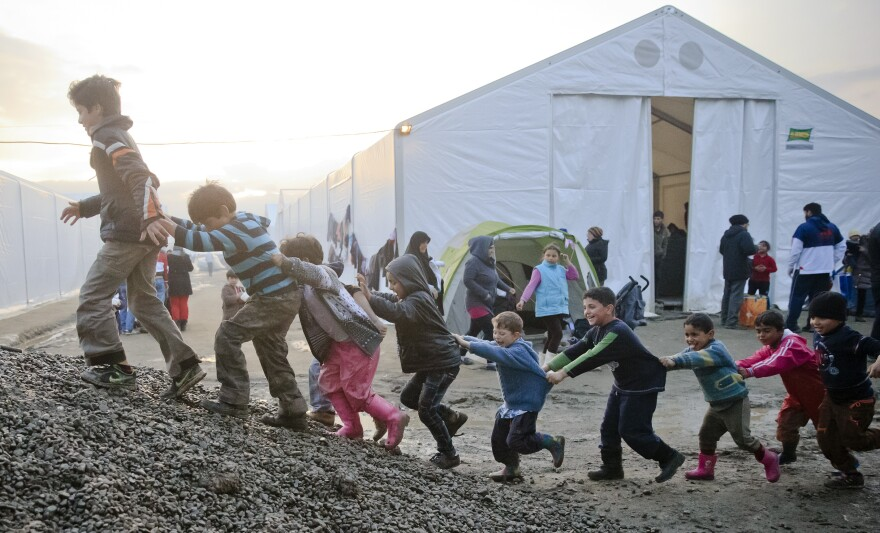 Children play on a pile of gravel at the northern Greek border point of Idomeni on Friday. More than 46,000 people are trapped in Greece, after neighboring countries stopped letting through refugees.