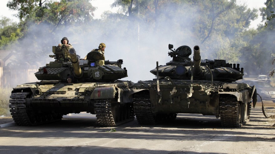 Pro-Russian rebels drive a tank in the town of Luhansk, eastern Ukraine, Sunday. Outside of areas that saw continued shelling, a semblance of normality has returned to parts of eastern Ukraine, thanks to a week-old cease-fire.