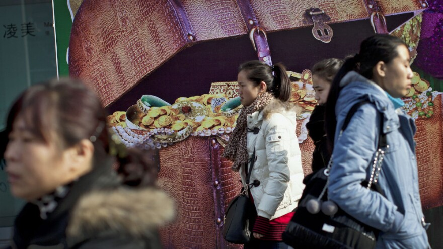 Chinese women walk past a billboard showing a box full of gold coins and jewelry, outside a shopping mall in Beijing on Thursday. Chinese leaders are scrambling to shore up flagging economic growth as exports weaken, abruptly reversing course after they spent two years struggling to cool an overheated expansion and surging inflation.