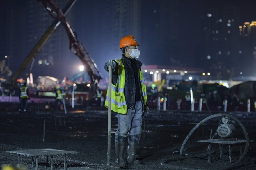 A construction worker rests at the site of the Huoshenshan temporary field hospital being built